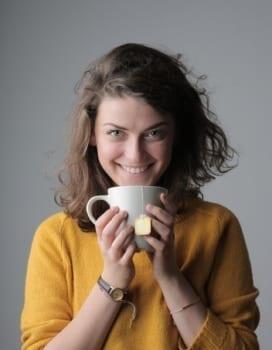 woman in yellow sweater holding white ceramic mug 3981440