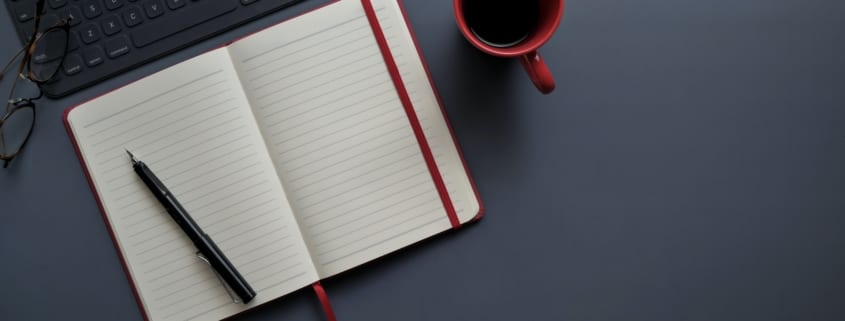 notebook and pen beside red mug on gray surface 3774057